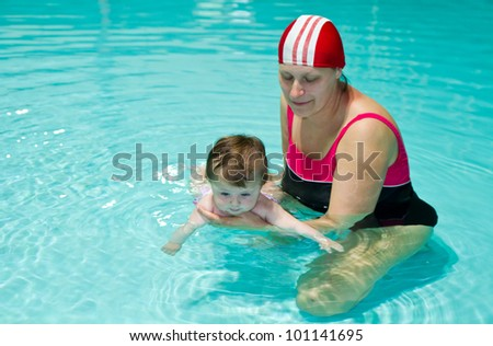 Young family with baby having fun in the swimming pool