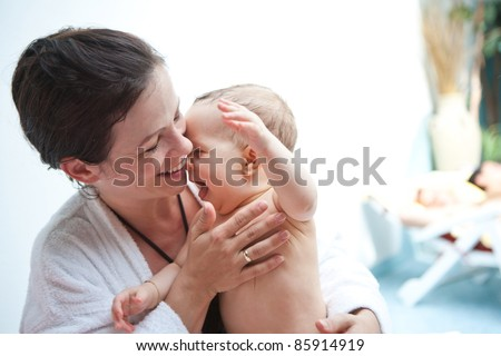 Young family with baby having fun in the swimming pool. - stock photo