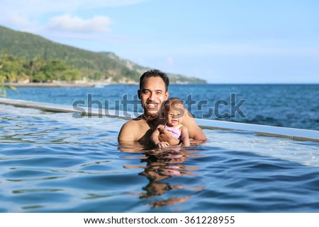 Young family with baby having fun in the swimming pool on summer day - stock photo