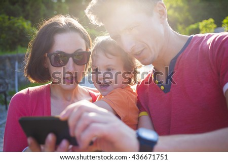 Young family with baby make a photo on the phone.