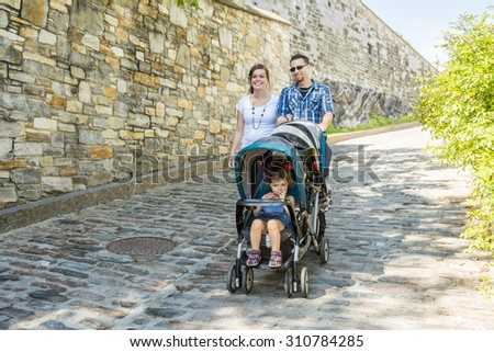 young family with baby strollers on city walk - stock photo