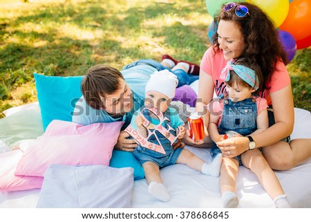 Young family with daughter and son having fun with pillows and colored balloons outdoors. Parents with two children relax in a summer garden. Mother, father, little girl and baby boy playing in park.