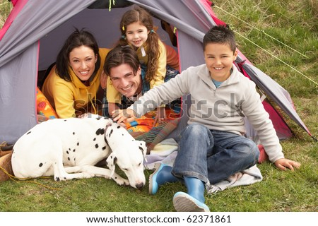 Young Family With Dog Relaxing Inside Tent On Camping Holiday - stock photo