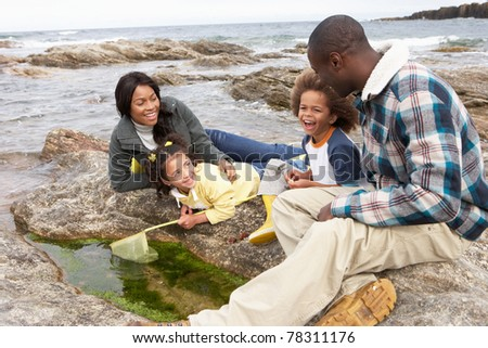 Young family with fishing net on rocks - stock photo