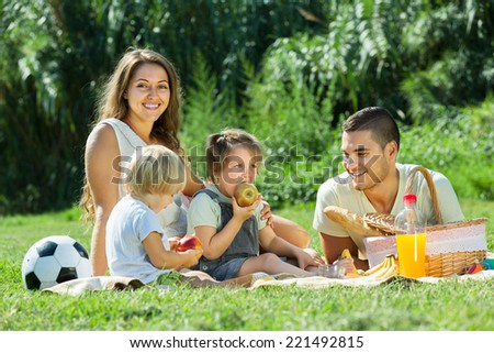 Young family with little daughters having holiday with picnic - stock photo