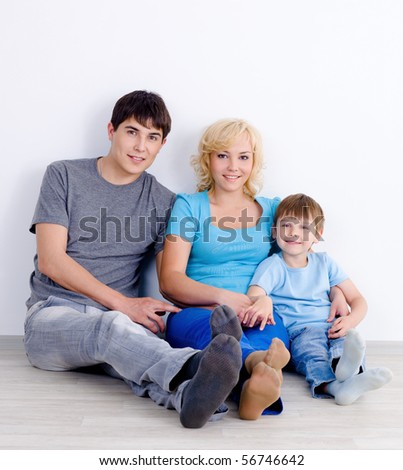 Young family with son sitting together on the floor near the wall with smile - indoors - stock photo