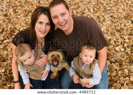 Young family with twin boys and pet dog in autumn leaves
