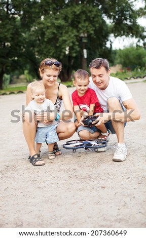 Young family with two boys playing with RC quadrocopter toy  - stock photo