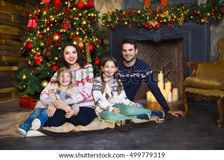 Young family with two children near fireplace celebrating Christmas. Love and relationship concept.