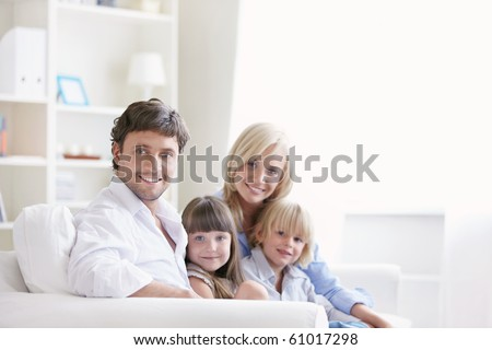 Young family with two children on a white sofa at home - stock photo
