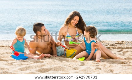 Young family with two children playing on the beach a summer day - stock photo