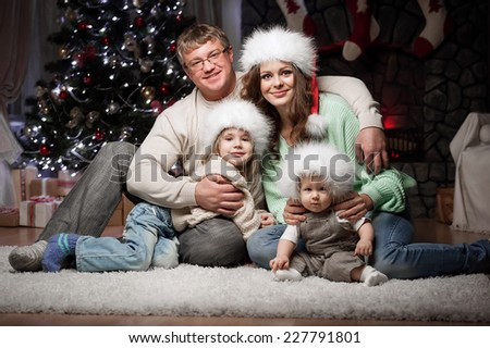 Young family with two children sitting at home New Year's Eve by the fireplace and near the elegant tree - stock photo