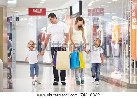 Young family with two children walking to the shops - stock photo