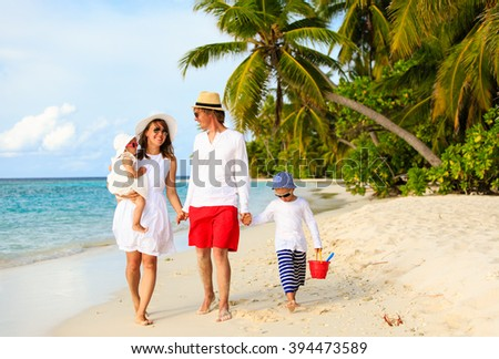 Young family with two kids walking at tropical beach - stock photo