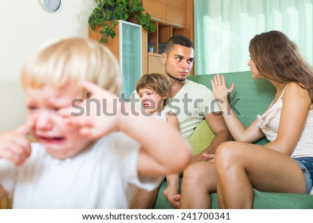 Young family with two little daughters having quarrel in the living room. Focus on man  - stock photo