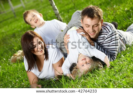 Young family with two small children frolics on a lawn