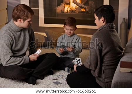 Young family with 4 years old kid playing card game at home in a cold winter day. - stock photo