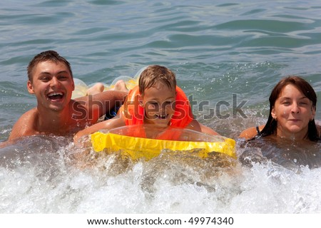 young family with yellow mattress bathes in sea. happy mum daddy and son play in water