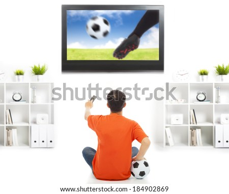 young fan watching soccer game at home - stock photo