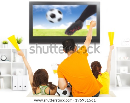 young fans watching soccer game and yell at home - stock photo