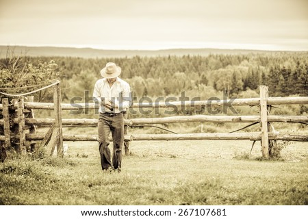 Young Farmer and a Chicken at the Farm - stock photo
