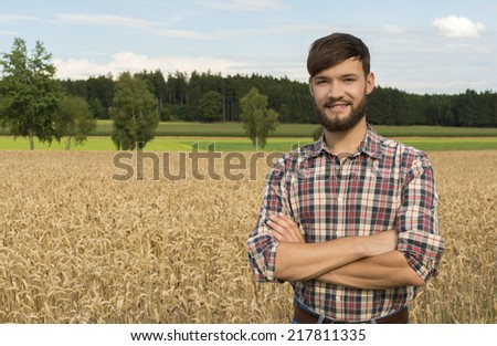 Young farmer at the corn field, Outdoor Shot - stock photo
