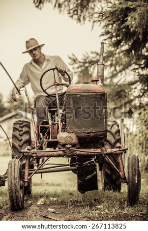 Young Farmer Driving a Red Old Vintage Tractor - stock photo
