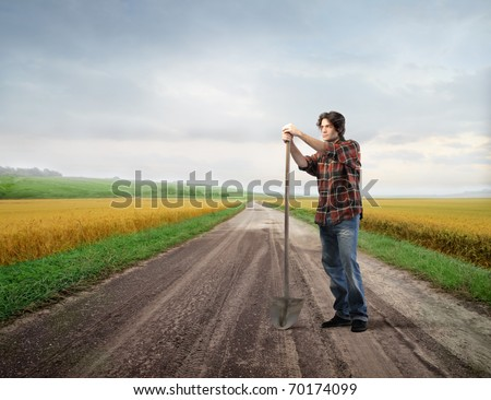 Young farmer holding a shovel with fields on the background - stock photo