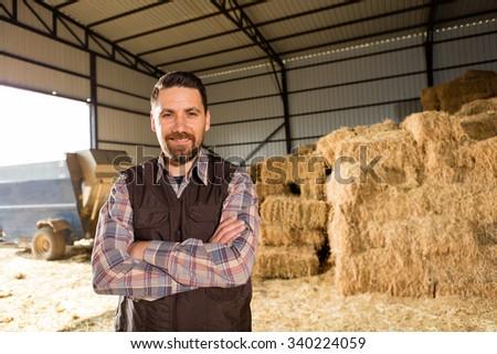 Young farmer in hayloft. - stock photo