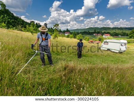 Young farmer mowing the lawn with a trimmer - stock photo