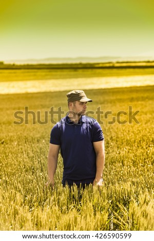 Young farmer on field of wheat