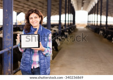 Young farmer showing tablet. - stock photo