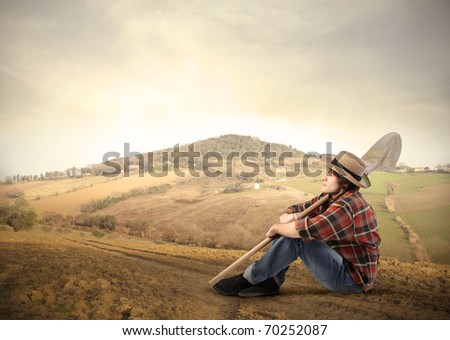 Young farmer sitting on a hill - stock photo