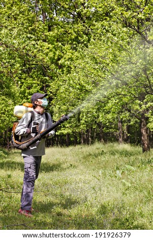 Young farmer spraying the trees with chemicals in orchard - stock photo