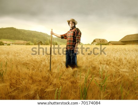 Young farmer standing on a wheat field - stock photo