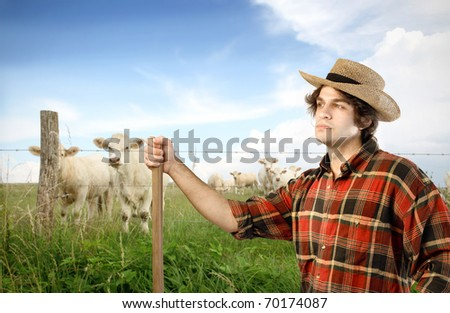 Young farmer with animals on the background - stock photo