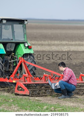 Young farmer working on laptop on farmland beside tractor - stock photo