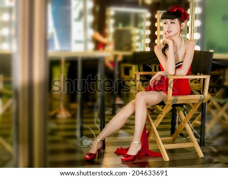 Young fashion asian model with cosmetics at dressing room - stock photo