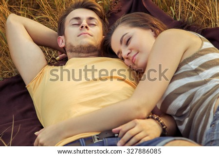 Young fashion beautiful loving casual style couple lying down on floral field in autumnal park, warm sunny day, enjoying family, romantic date, love concept. relaxing and rest, closed eyes sleeping. - stock photo