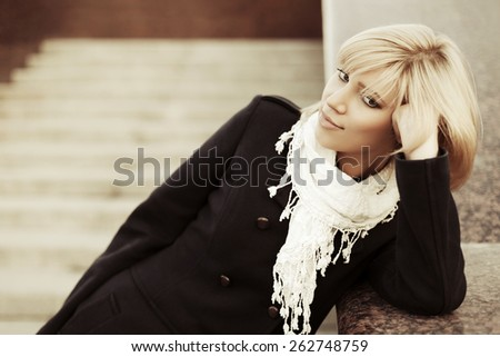 Young fashion blond woman in black coat daydreaming on the steps - stock photo