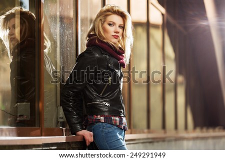 Young fashion blond woman in leather jacket at the mall window - stock photo