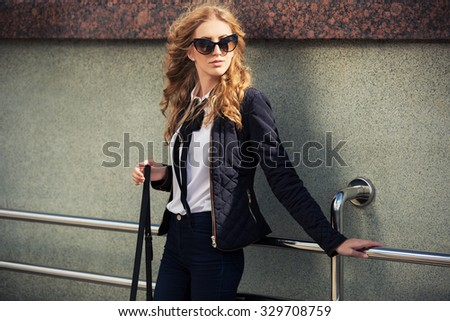 Young fashion blond woman in sunglasses at the wall