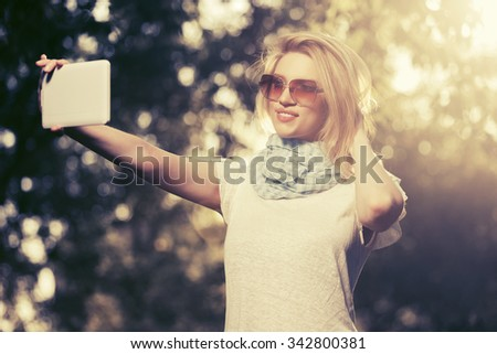 Young fashion blond woman taking a selfie with tablet computer outdoor - stock photo