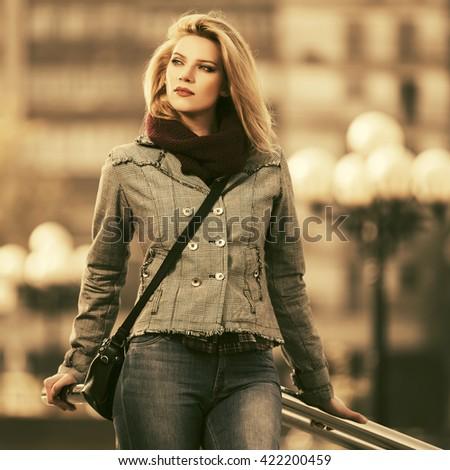 Young fashion blond woman walking on city street - stock photo