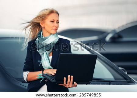 Young fashion blonde business woman with laptop by her car - stock photo