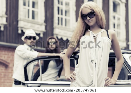 Young fashion blonde woman next to retro car