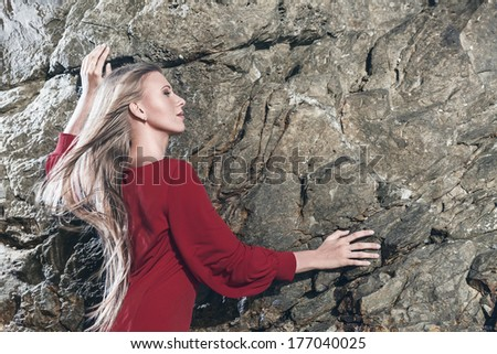 Young fashion blonde woman posing in red mini dress in front of stone background