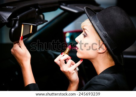 young fashion blonde woman with hat applying red lipstick using car mirror - stock photo
