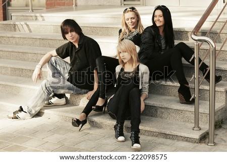 Young fashion boy and girls sitting on the steps  - stock photo