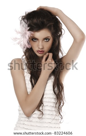 young fashion brunette posing on white wearing a pink feather in her hair - stock photo